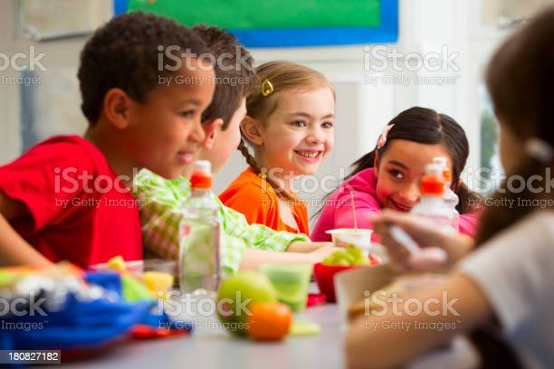 Young Students Enjoying Their Lunch At School Stock Photo - Download Image Now