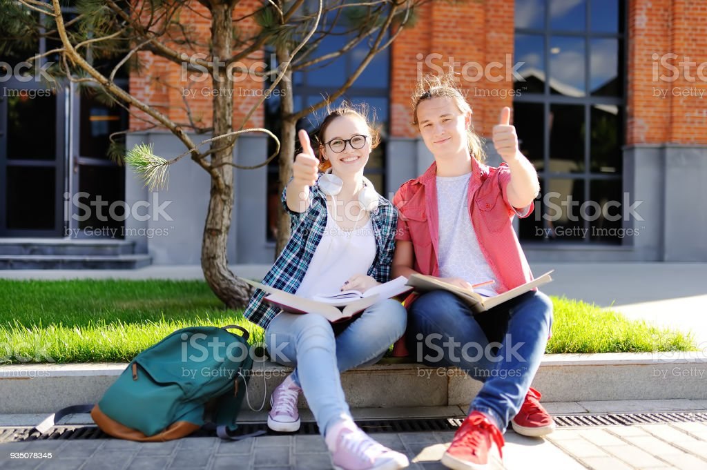 Young students show sight thumbs up and good luck stock photo