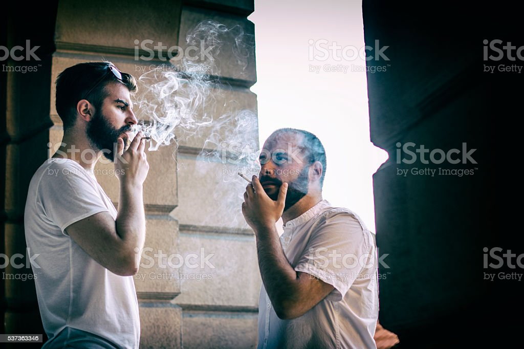 Young students smoking cigarettes on balcony stock photo