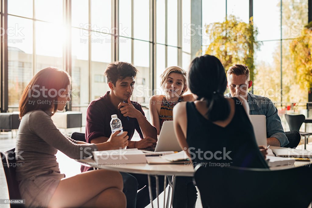 Young students studying around a table in library stock photo
