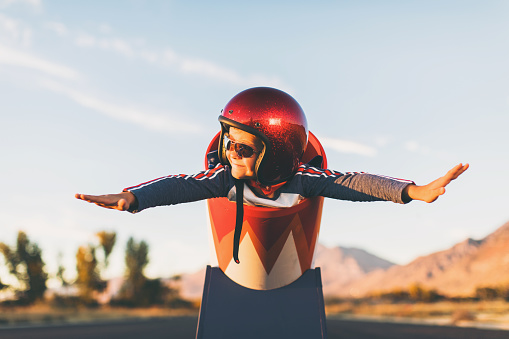 A young boy dressed in helmet and flight goggles sits ready for flight in a homemade cannon. His arms are outstretched and ready for take off as he is excited to explore new heights. Image taken on a rural road in Utah, USA.