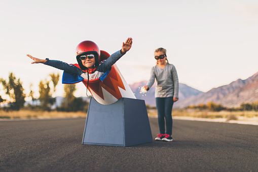 A young boy dressed in helmet and flight goggles sits ready for flight in a homemade cannon while his sister is ready to light the fuse. His arms are outstretched and ready for take off as he is excited to explore new heights. Image taken on a rural road in Utah, USA.