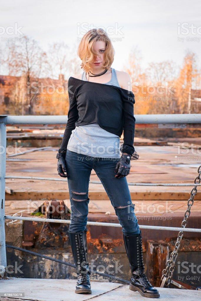Genç şık agresif görünümlü kadın. Bağcıklı çizmeler, siyah deri eldiven, kot pantolon, sarışın saç sökük. royalty-free stock photo