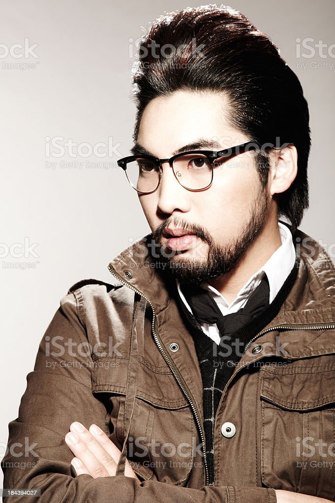 Young stylish Asian man with retro glasses and hairstyle royalty-free stock photo