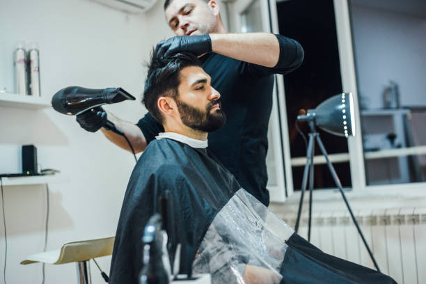 Young stylish barber with mustache and tattoos giving man haircut stock photo