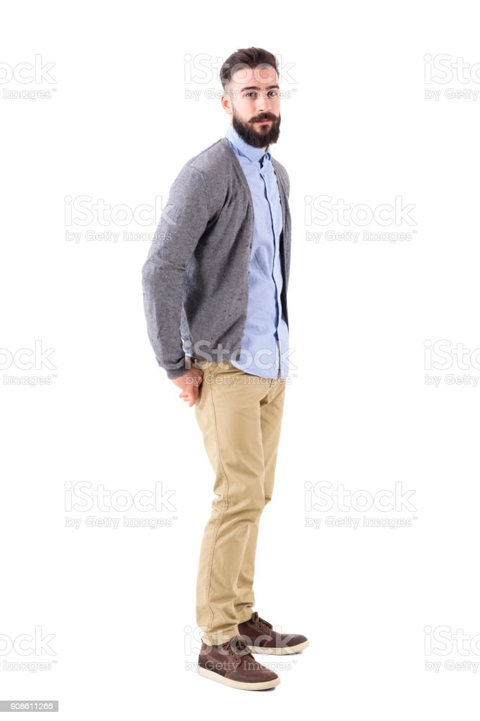 Young stylish bearded man in cardigan with hands in back pockets looking at camera. stock photo
