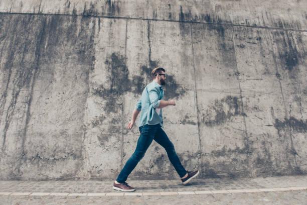 stilvolle bärtigen jüngling ist zum meeting hetzen. er ist in einem casual-outfit, mit brille, gehen im freien - druck jeans stock-fotos und bilder