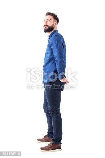 931173966istockphoto Young stylish bearded smart casual man watching above with hands in back pockets. 931178710