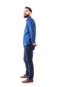 istock Young stylish bearded smart casual man watching above with hands in back pockets. 931178710