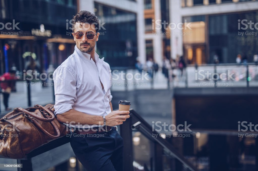 Young stylish businessman having takeaway coffee One young handsome businessman drinking takeaway coffee on the street 25-29 Years Stock Photo