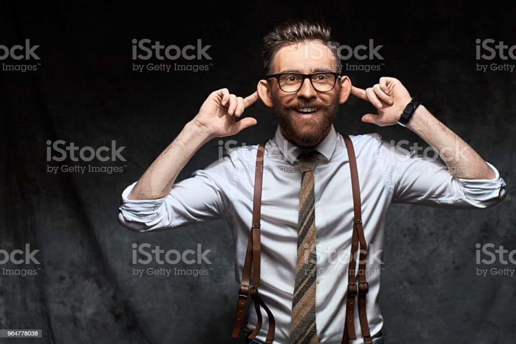 Young stylish businessman or manager holds his necktie in hand as if he decided to hang himself on it conceptually showing high level of stress and overwork royalty-free stock photo
