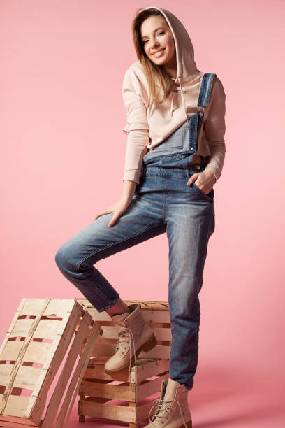 Young stylish cheerful woman in denim overalls made of denim and in beige sweatshirt on a pink background with wooden boxes stock photo