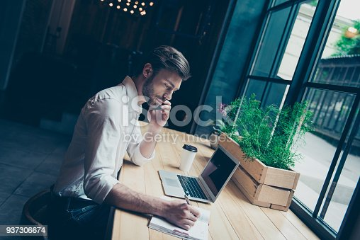 937328186 istock photo Young stylish entrepreneur in formal wear is sitting at his work place in a loft styled modern coworking and writes down the data, talks on the phone 937306674
