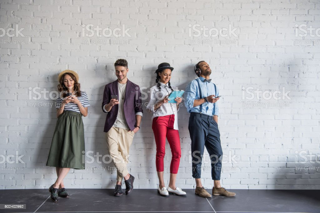 young stylish friends using digital devices while standing near brick wall stock photo