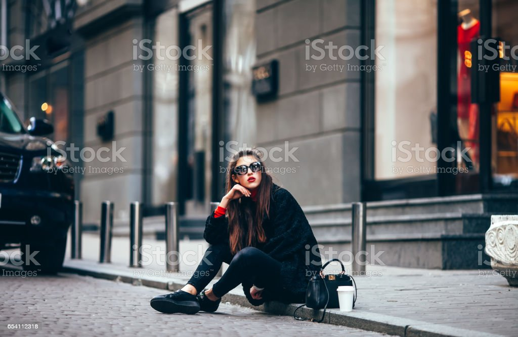 young stylish girl, passing by the Windows.Wearing fashionable glasses and a black coat.Keeps coffee. looks at camera stock photo