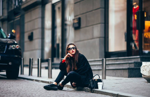 young stylish girl, passing by the windows.wearing fashionable glasses and a black coat.keeps coffee. looks at camera - paris fashion stock photos and pictures