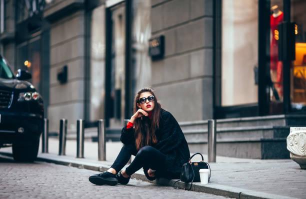 chica joven con estilo, pasando por las ventanas. usando gafas de moda y un abrigo negro. mantiene el café. mira la cámara - moda parisina fotografías e imágenes de stock