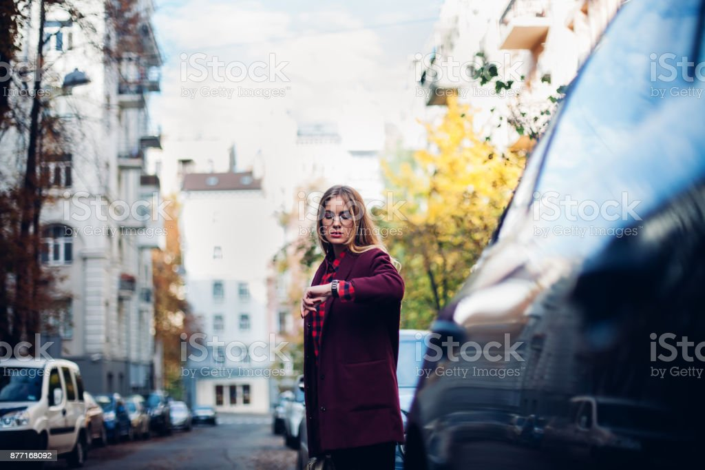 young stylish girl stands by the road, looks at her watch, waits for a taxi. stock photo