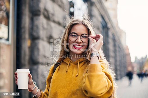 870648602 istock photo young stylish girl student wearing bright yellow sweatshirt.Close-up portrait of inspired young woman laughing and touching glasses She holds coffee to go 888124070