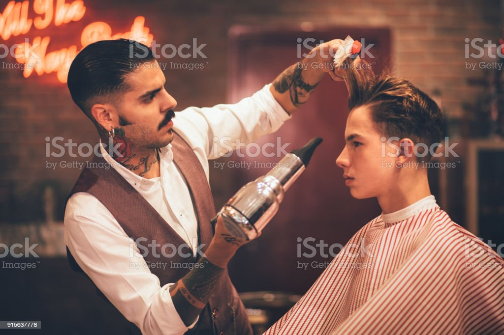 Young stylish hairdresser blow drying hipster man's hair stock photo