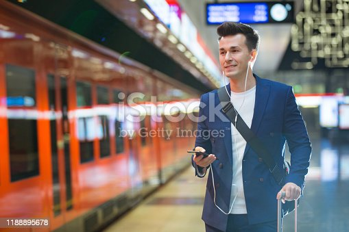 Young stylish handsome man in suit with suitcase standing on metro station holding smart phone in hand, scrolling and texting, smiling and laughing on subway station. Finland