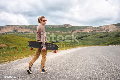 Young stylish hipster with long hair and sunglasses, walking with a long board in his hands on a rural asphalt road in the mountains against the background of epic rocks