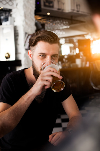 Young stylish man drinking beer
