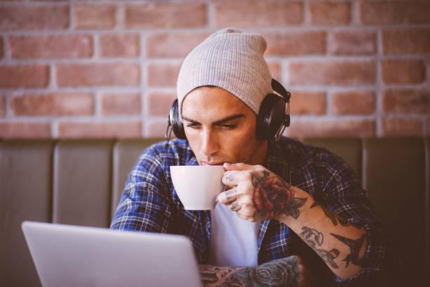 stilvolle jüngling kaffee zu trinken und musik hören - kaffeetasse tattoo stock-fotos und bilder