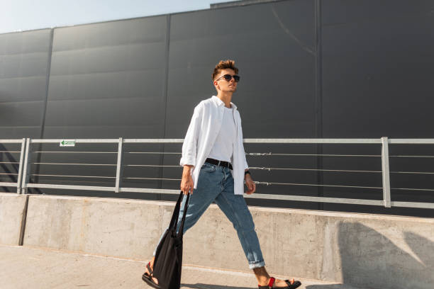 Young stylish man hipster in trendy clothes in sunglasses with a black cloth bag in vintage sandals walks is in a city near a gray building. American guy. Fashionable summer menswear. Street style. Young stylish man hipster in trendy clothes in sunglasses with a black cloth bag in vintage sandals walks is in a city near a gray building. American guy. Fashionable summer menswear. Street style. menswear stock pictures, royalty-free photos & images