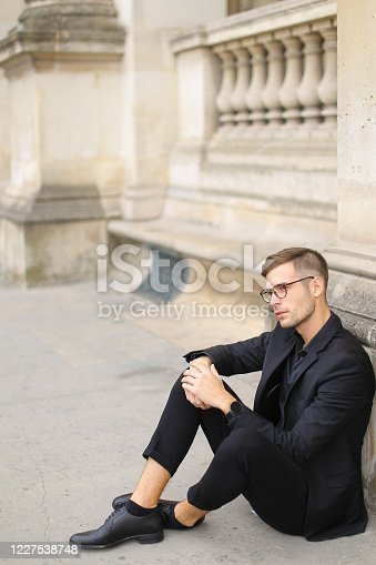 665586146 istock photo Young stylish man sitting on sidewalk ground and wearing black suit 1227538748