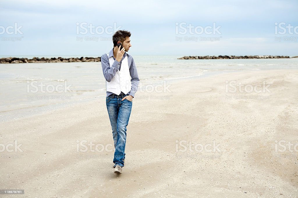 Young stylish man using mobile phone and walking on beach stock photo