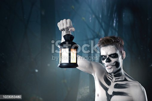 Young stylish man with art grimm for hallowen party. Fashion body art. Face art. dead man with a lantern on the background of a scary forest