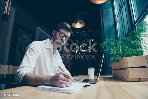 937328186 istock photo Young stylish well dressed author writer is working in a modern coworking, writing the novel, in glasses, so serious and focused 937326608
