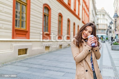 531098549 istock photo Young stylish woman drinking coffee to go in a city street 1168015883