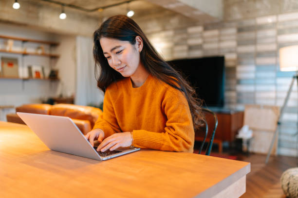 Young stylish woman using laptop at home stock photo