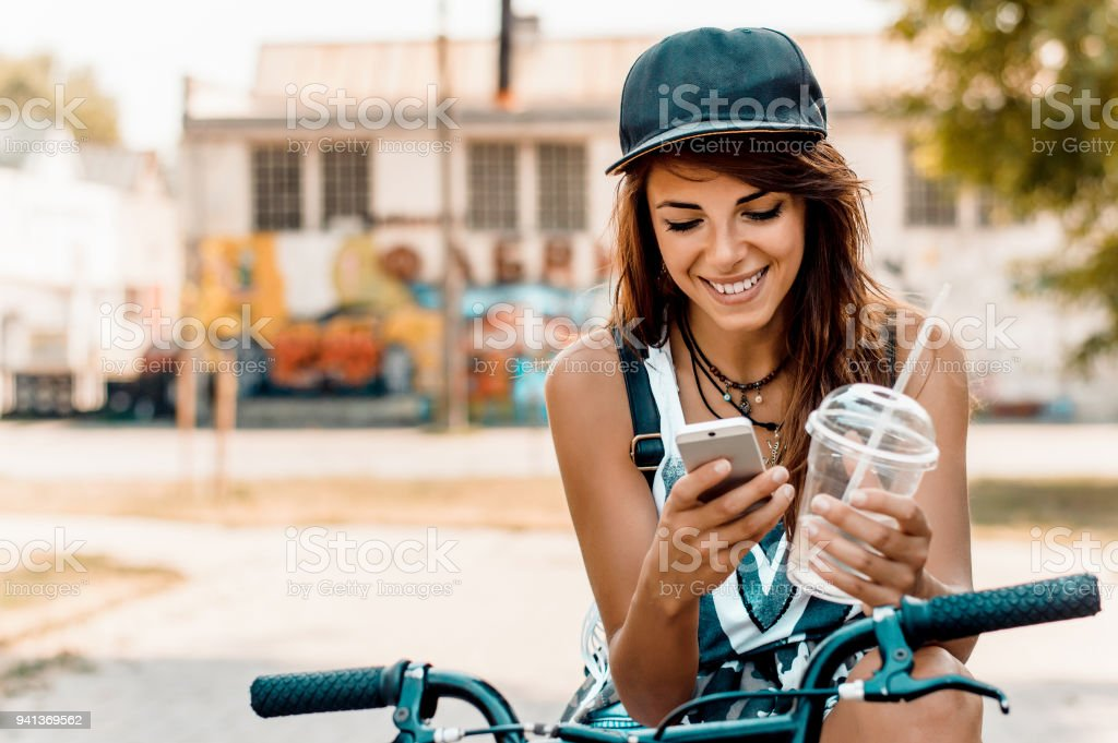 Young stylish woman with a bicycle using cell phone. stock photo