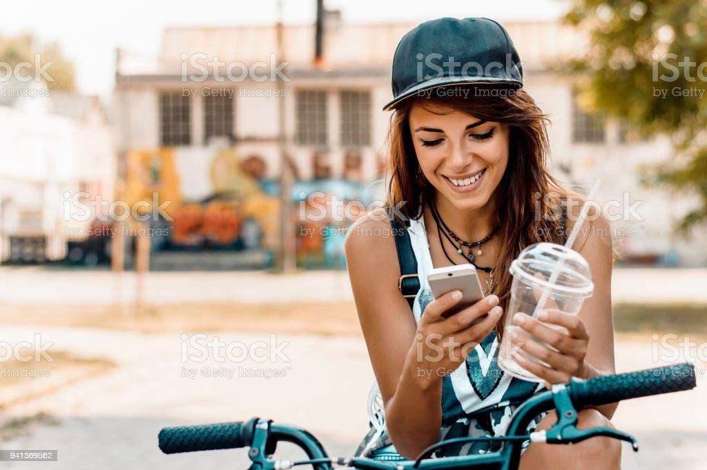 Junge stilvolle Frau mit dem Fahrrad mit Handy. – Foto