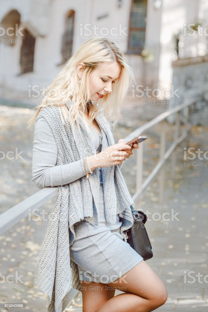 Young stylish woman with smart phone the street stock photo
