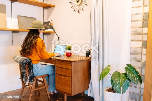 A young stylish woman is working om a laptop remotely from home.