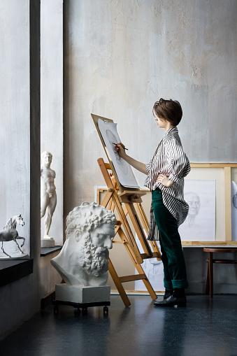 istock Young successful artist in art workshop studio 1128445507
