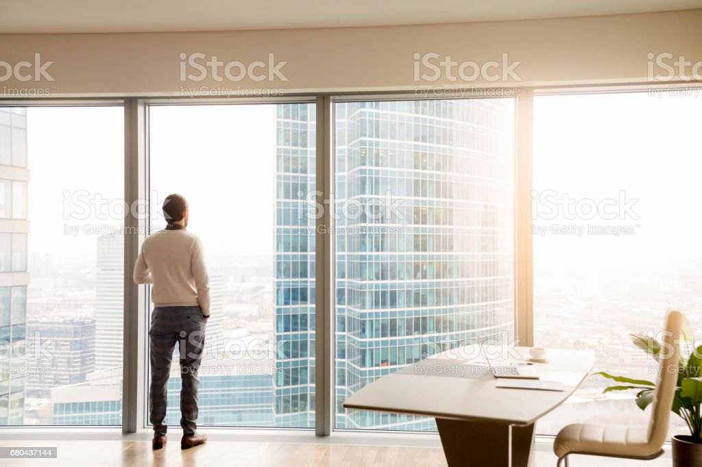 Young successful businessman standing in office looking at full-length window ストックフォト