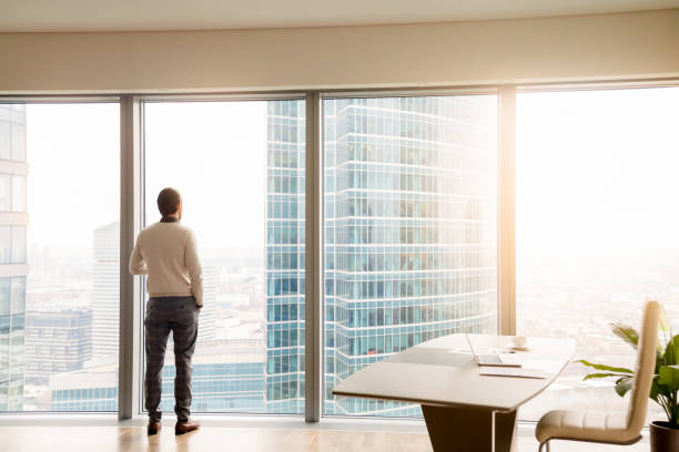 Young successful businessman standing in office looking at full-length window stock photo