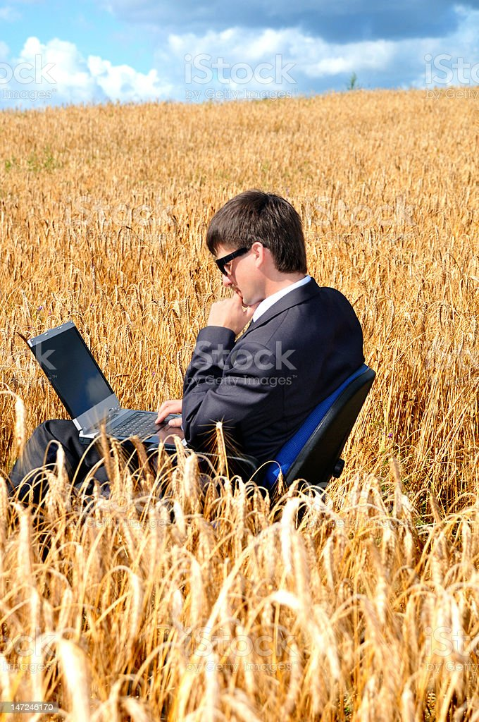 Young successful businessman works in field on notebook royalty-free stock photo