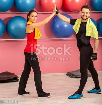 670054434istockphoto Young Successful Couple in a Gym 1182225137