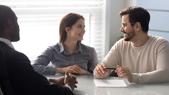 843533912 istock photo Young successful couple, man and woman discuss terms of contract. 1263543042