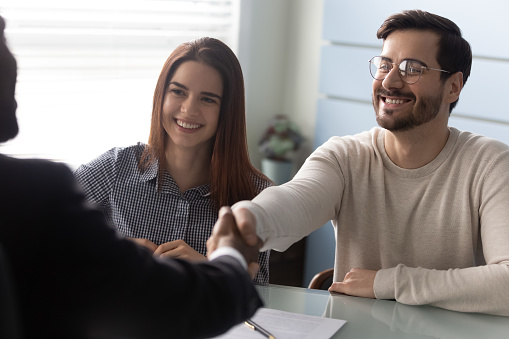 843533912 istock photo Young successful couple, man and woman shaking hands with businessman. 1263543046