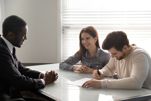 843533912 istock photo Young successful couple, man and woman sign up document. 1263543037
