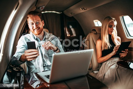 istock Young successful couple working while travelling aboard a private jet 1076581994