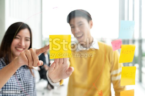 istock Young successful creative man and woman smile and brainstorm on project at office pointing hand or finger to yellow post note or sticky note. Close up view couple sharing idea on glass wall concept. 1060966134