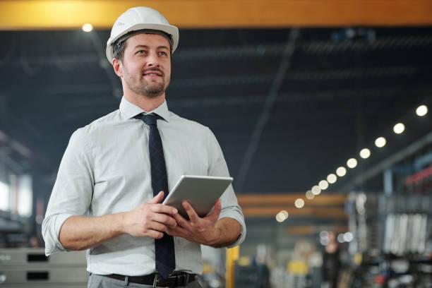 Junger erfolgreicher eleganter Vorarbeiter mit Touchpad, das mit Daten in der Fabrik arbeitet – Foto